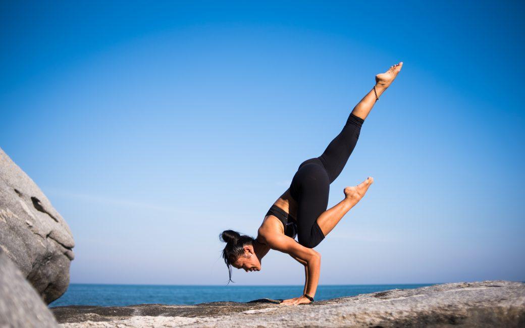 woman in yoga pose near ocean
