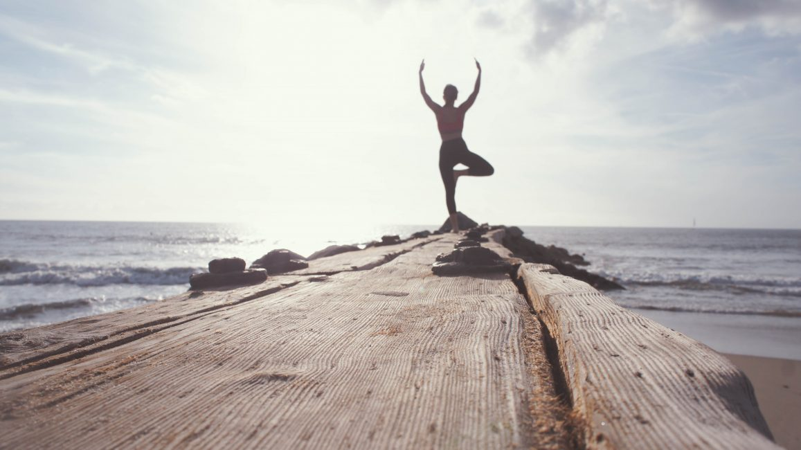woman in yoga pose at end of boardwalk