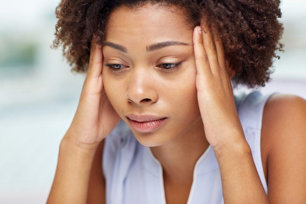 woman with headache rubbing her head