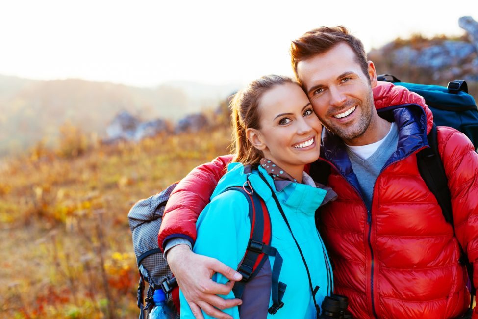 Young couple in mountains smiling