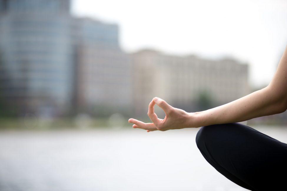 hand resting on knee in meditation pose